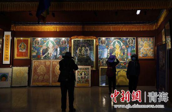 图为:游客在活动中参观热贡唐卡。