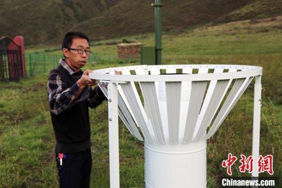 图为班玛县气象局工作人员在维护藏雪茶基地气候站。青海省气象局供图