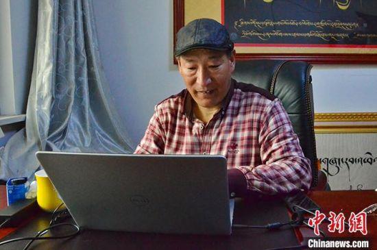 4月15日,扎西才仁在玉树州金巴慈善会的办公室内工作。中新社记者 鲁丹阳 摄