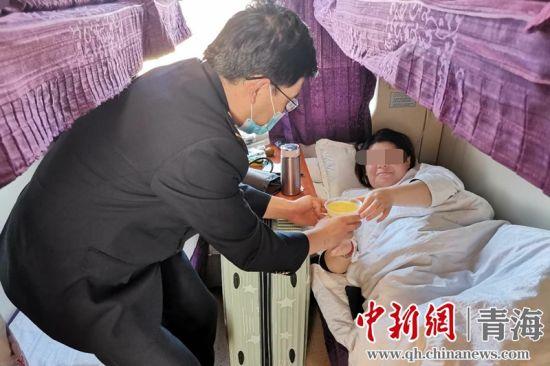 图为列车员为孕妇递送食物。青藏集团公司供图