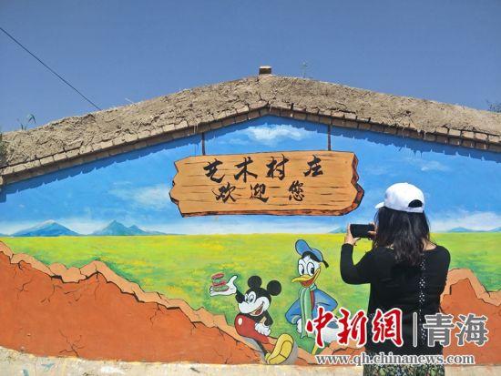 图为游客与涂鸦作品合拍留念。 祁增蓓摄