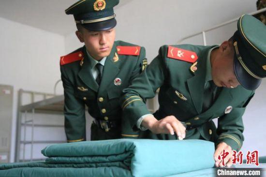 图为老兵教新兵叠被子。 马跃艺 摄