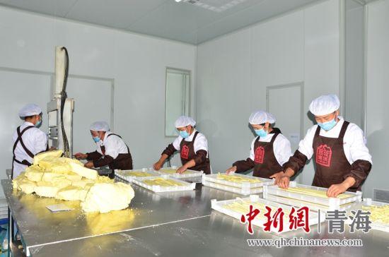 图为青海省海东市平安区三合镇扶贫产业示范园内的员工正在切割牦牛奶制品。 鲁丹阳摄