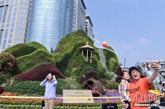 资料图:民众在北京东单国庆主题花坛前自拍留影。中新社记者 张兴龙 摄