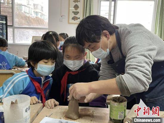 图为西宁市劳动路小学教师贾煜与学生一起制作陶艺。 周瑞辰子 摄