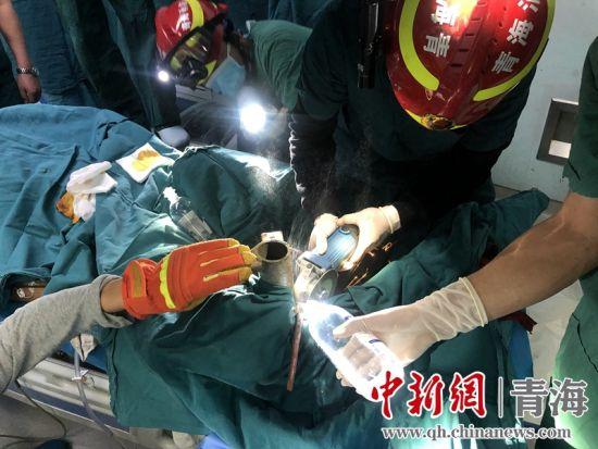 图为消防救援人员正在浇生理盐水冷却摩擦产生的热量。 西宁消防救援支队供图