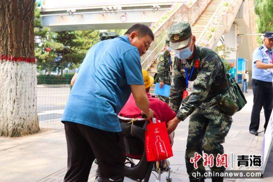 图为武警官兵帮老人撤离警戒线。刘进峰摄