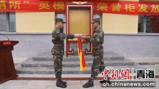 图为火箭军某部队长向哨所班长颁受荣誉锦旗。 高翔摄